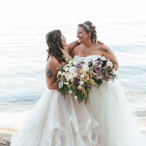 Two brides at waterside wedding