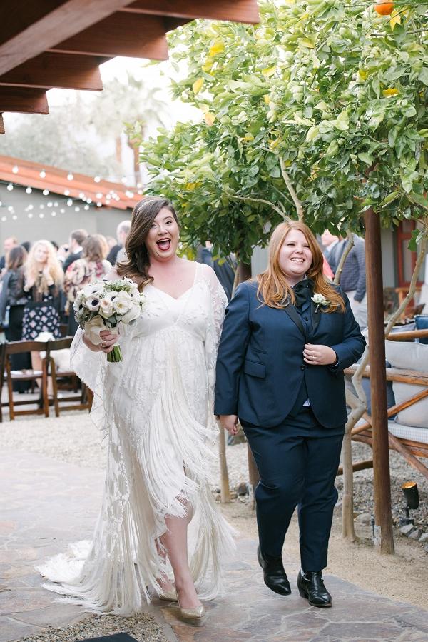 Newlywed Couple In Fringed White Dress And Indigo Suit
