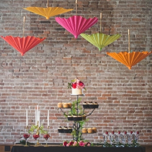 A whimsical dessert display with a cupcake tower and hanging parasols
