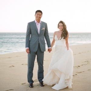 A Bride and Groom Holding Hands on the Beach