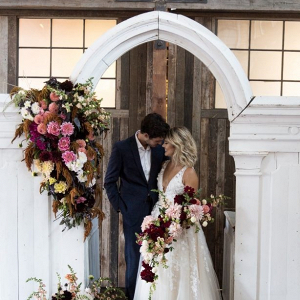 Vintage arch ceremony backdrop with lush florals