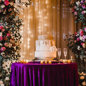 Gold and white wedding cake under floral arch