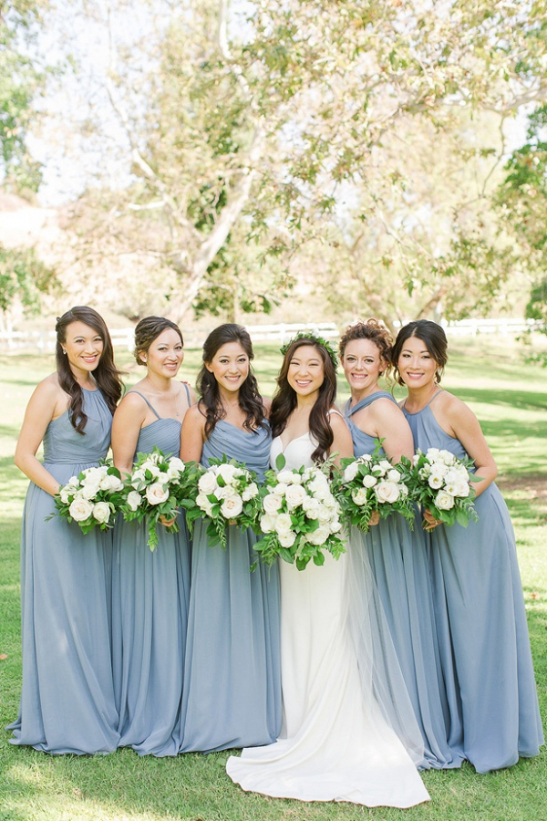 Bridesmaids in light blue dresses and white and green bouquets