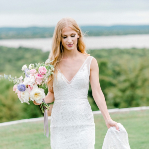 Bride in v-neck lace gown and pastel bouquet