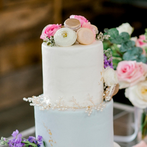 Pastel wedding cake with ranunculus and macaron topper