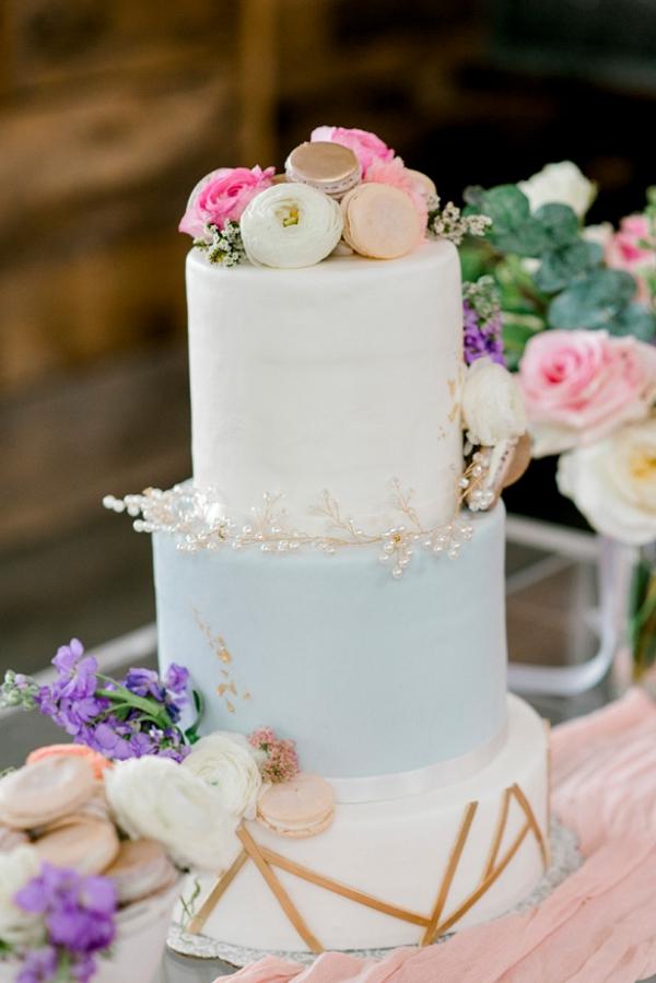 Pastel wedding cake with ranunculus and macaron topper