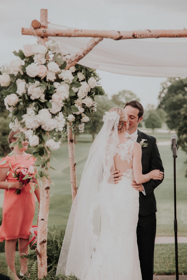 Outdoor wedding ceremony with floral and draping chuppah