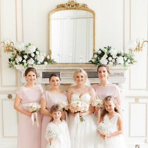 elegant bride with her bridesmaids in pale pink dresses and flower girls