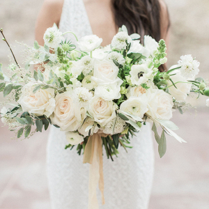 Elegant white bridal bouquet with soft golden silk ribbon