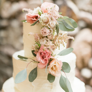 Jennie + Casey's beautiful tiered wedding cake adorned with flowers