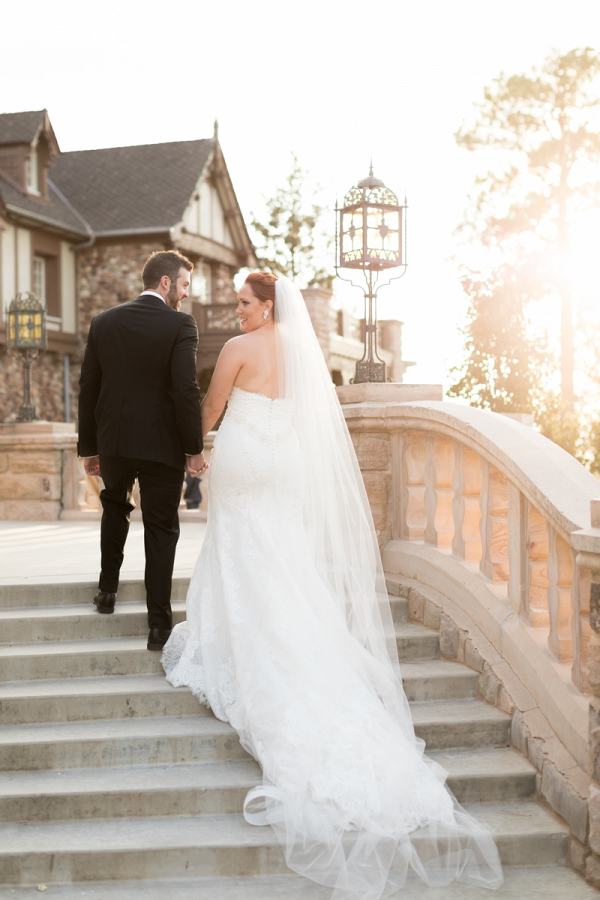bride and groom portrait on mansion steps with wedding dress train flowing