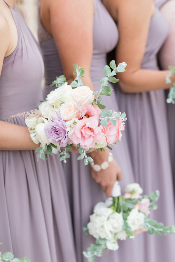 Beautiful bridesmaids wearing lilac and holding lovely little bouquets