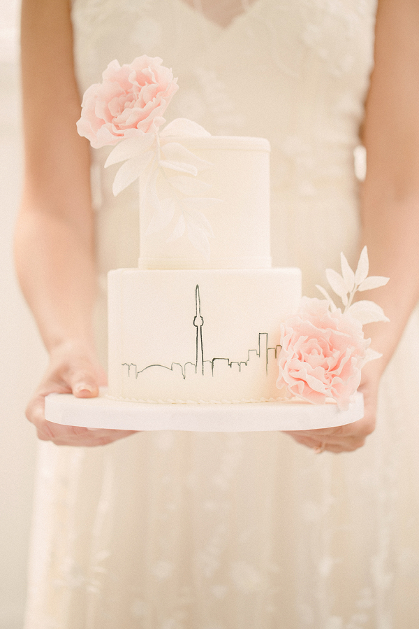 Romantic two tier wedding cake with cityscape illustration