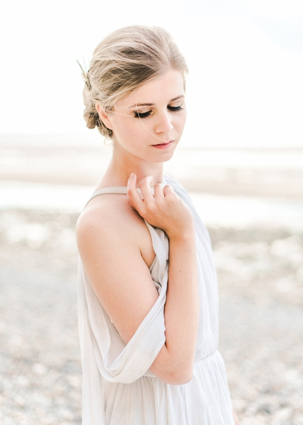Grecian inspired gown worn with loose updo for engagement session on the beach