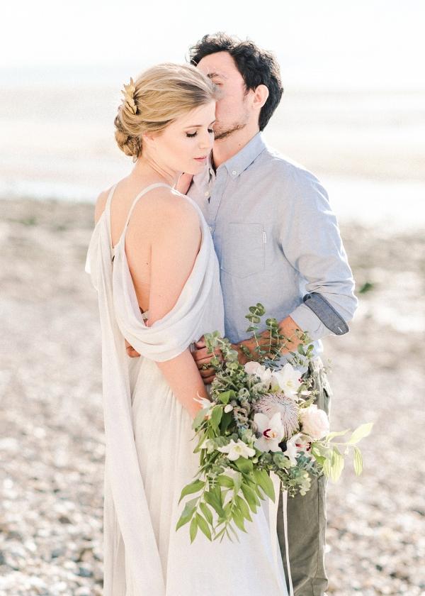 engagement session portrait of couple with floral bouquet