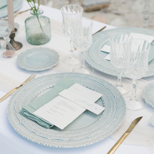 blue white and gold table decor details with blue charger plates and gold cutlery for a beach wedding
