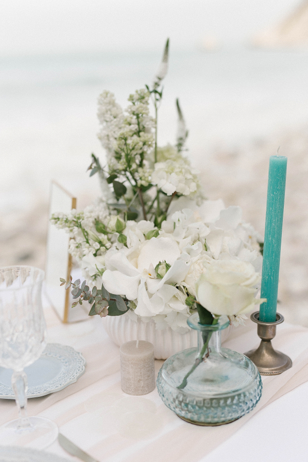 blue glass bud vase with white floral arrangement and blue tall taper candles for this beach wedding decor