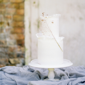 The beautiful fine art wedding cake by Yolk decorated with a spring of golden grass
