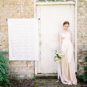 fine art bride wearing golden silk wedding gown leaning against an old wooden door