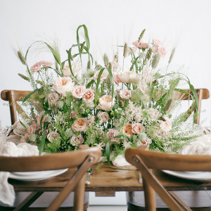statement floral centrepiece in peach and green with cross back chairs