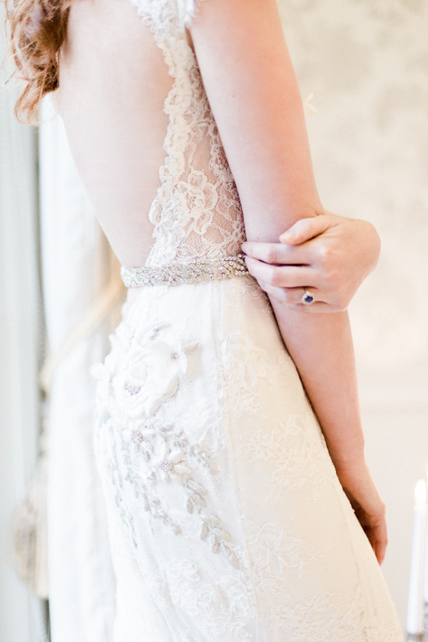 Dramatic low back lace wedding dress with beaded belt and sapphire engagement ring