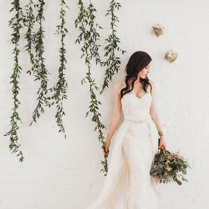 bridal portrit with modern backdrop of greenery hanging along the wall