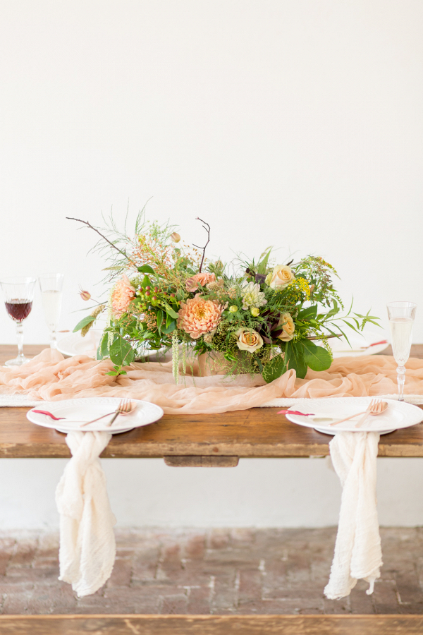 Rustic chic table setting with a fine art twist and peach colour palette floral centrepiece linen napkins and red wine
