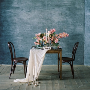 table setting against blue backdrop and decorated with pink orchid flowers