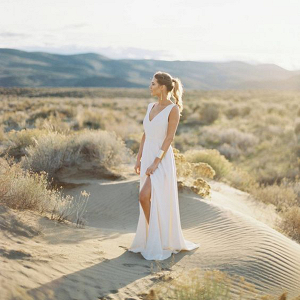 modern bride wearing sleek white wedding dress with statement gold cuff bracelet stood in the sand