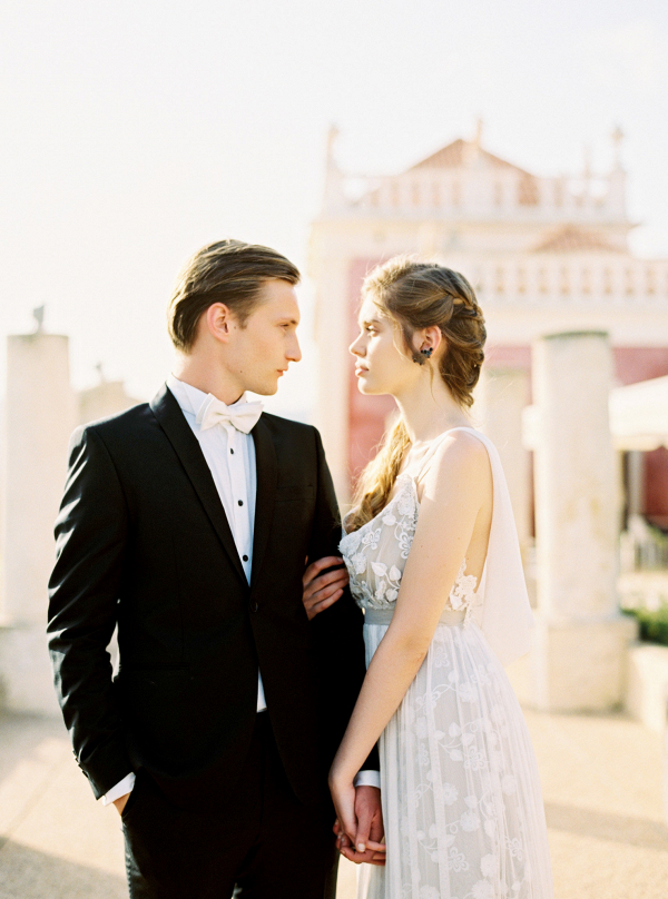 modern groo wearing black suit and fashionable bride wearing white embroidered gown with loose plaited hairstyle