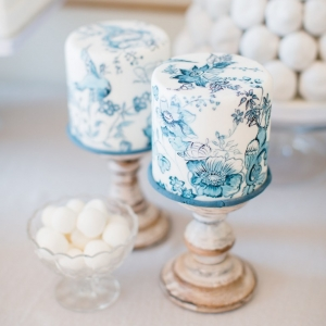 Handpainted individual wedding cakes with blue willow design on rustic wooden stands