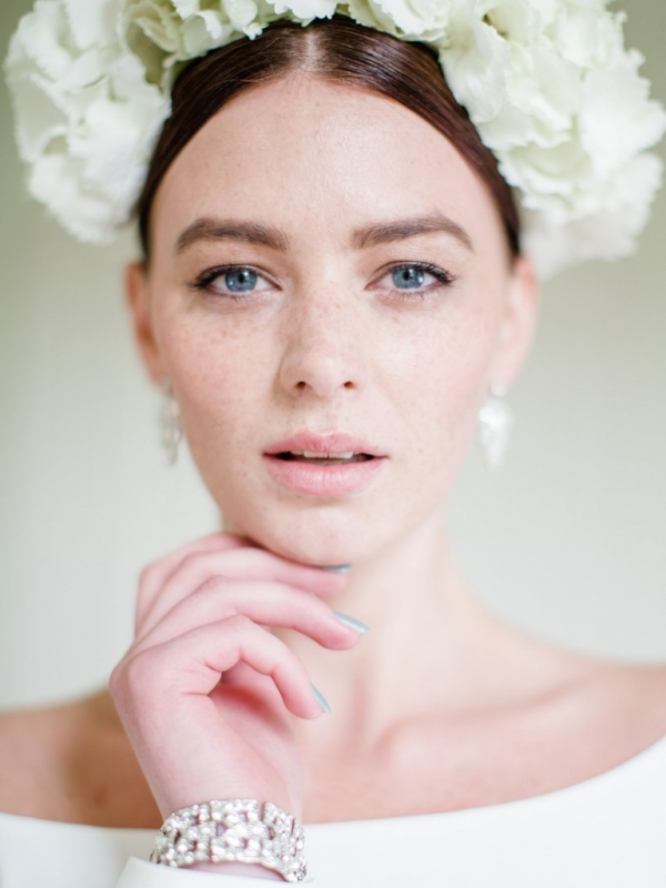 Bride wearing a classic white hydrangea crown with pearl drop earrings and something blue nail polishe
