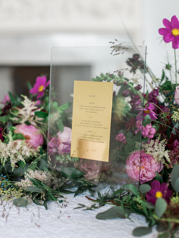 Elegant statement wedding menu design in gold displayed in the floral runner