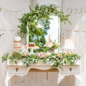 Rustic cake display with naked cakes and organic foliage on a vintage dresser