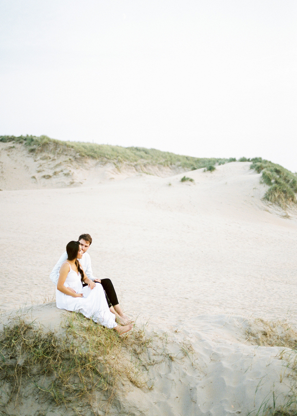 sitting in the sand dunes on the beach of their engagement shoot