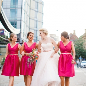 Contemporary city bride wearing David's Bridal and bridesmaids in pink