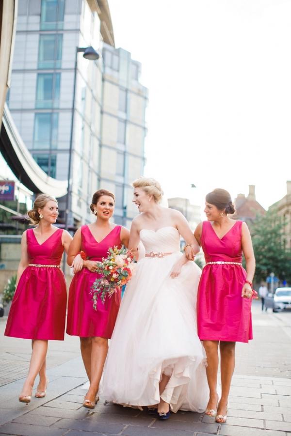 Contemporary city bride wearing David's Bridal and bridesmaids in pink