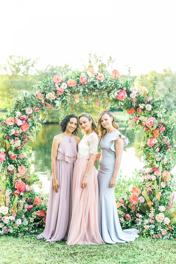 Beautiful pastel mix and match bridesmaids and a colourful floral arch!