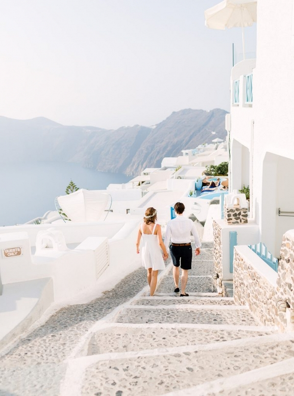couple walking hand in hand along the quaint streets of Santorini