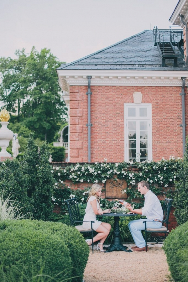 Couple sit in the beautiful gardens to celebrate with wine