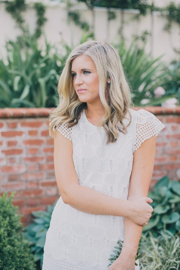 Beautiful portrait of Katlyn with landscaped gardens and exposed brick wall i the background