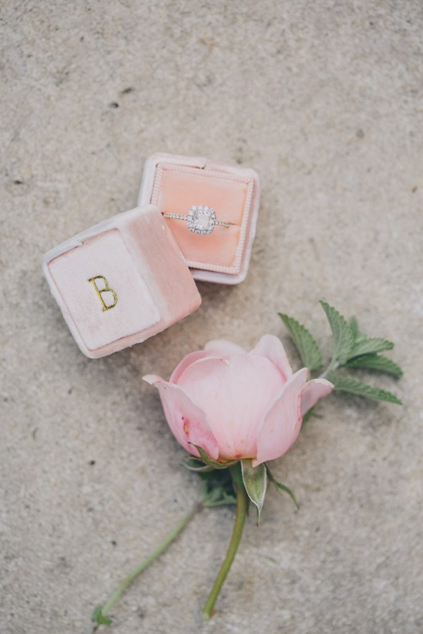 pink rose with engagement ring displayed in a velvet ring box