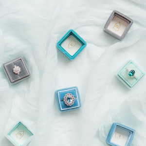 collection of engagement rings with coloured stones in velvet ring boxes