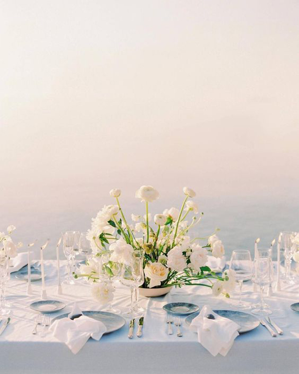 beach wedding table setting in blue with modern white floral centrepiece