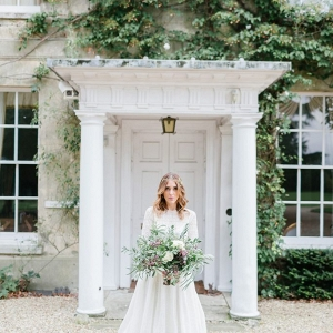 bridal portrait stood in the grand doorway of the manor house