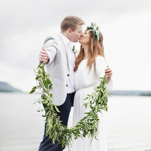 couple standing on the shore holding a wreath together