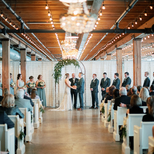 Modern industrial wedding ceremony with greenery arch