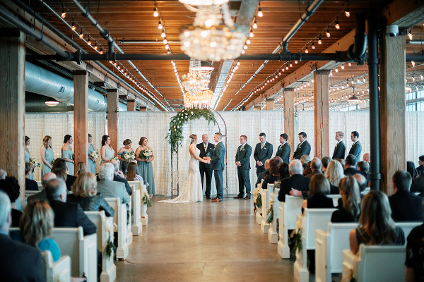 Modern industrial wedding ceremony with greenery arch