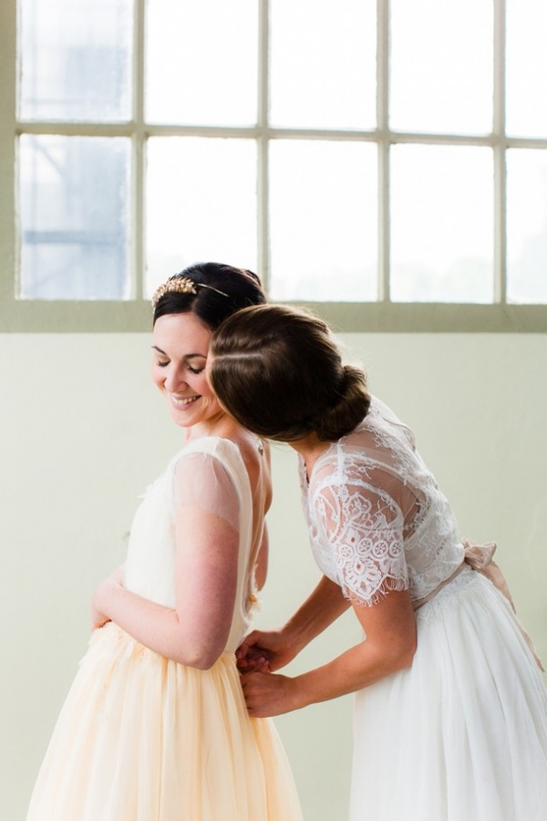 Classic bride in a yellow wedding dress with bridesmaid in white lace detailed dress