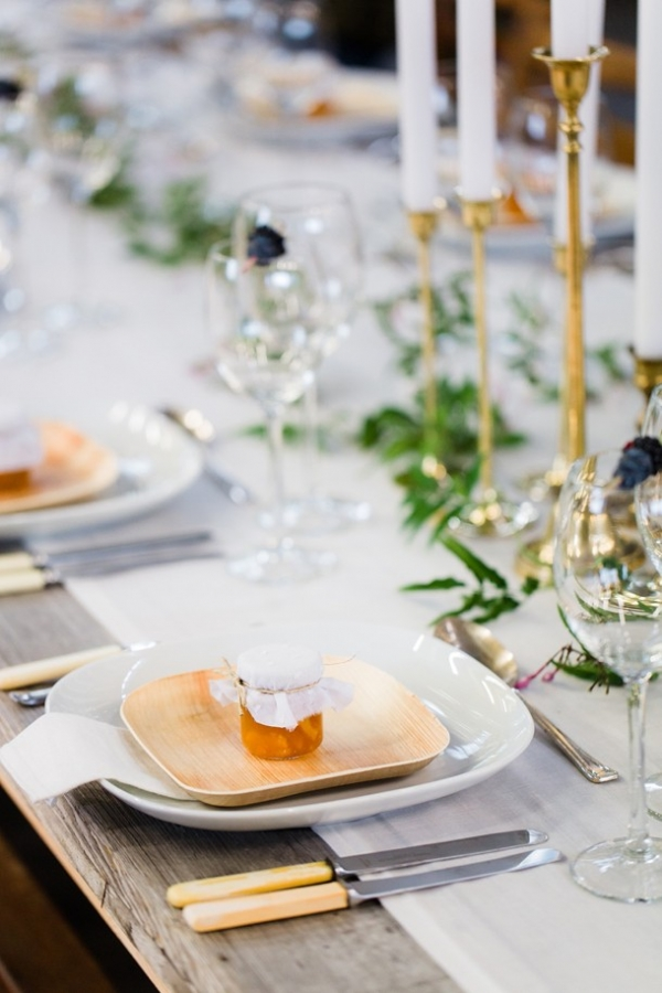 Urban organic wedding tables with a delicate jasmine floral runner, gold candlesticks and DIY honey pot favours